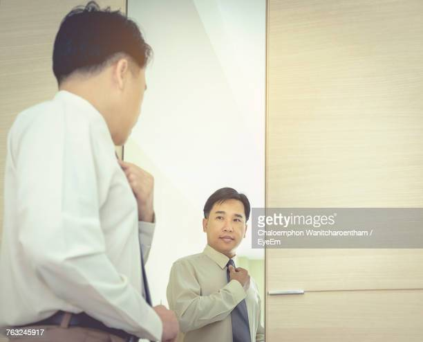 Low Angle View Of Businessman Looking Into Mirror Reflection