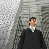 Low angle view of businessman next to building
