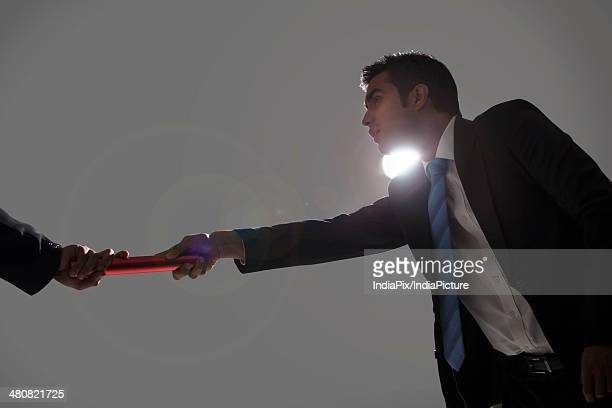 Low angle view of businessman passing baton to coworker