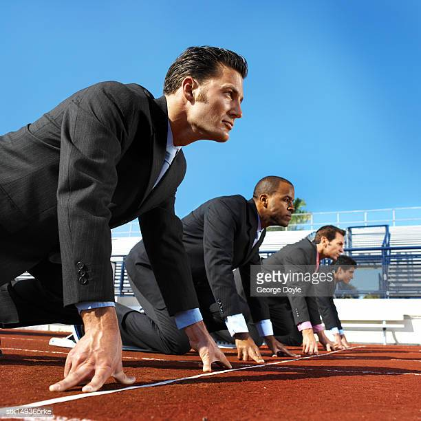 low angle view of businessmen at the starting position on a running track