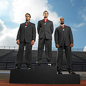 low angle view of businessmen standing in a stadium wearing  medals