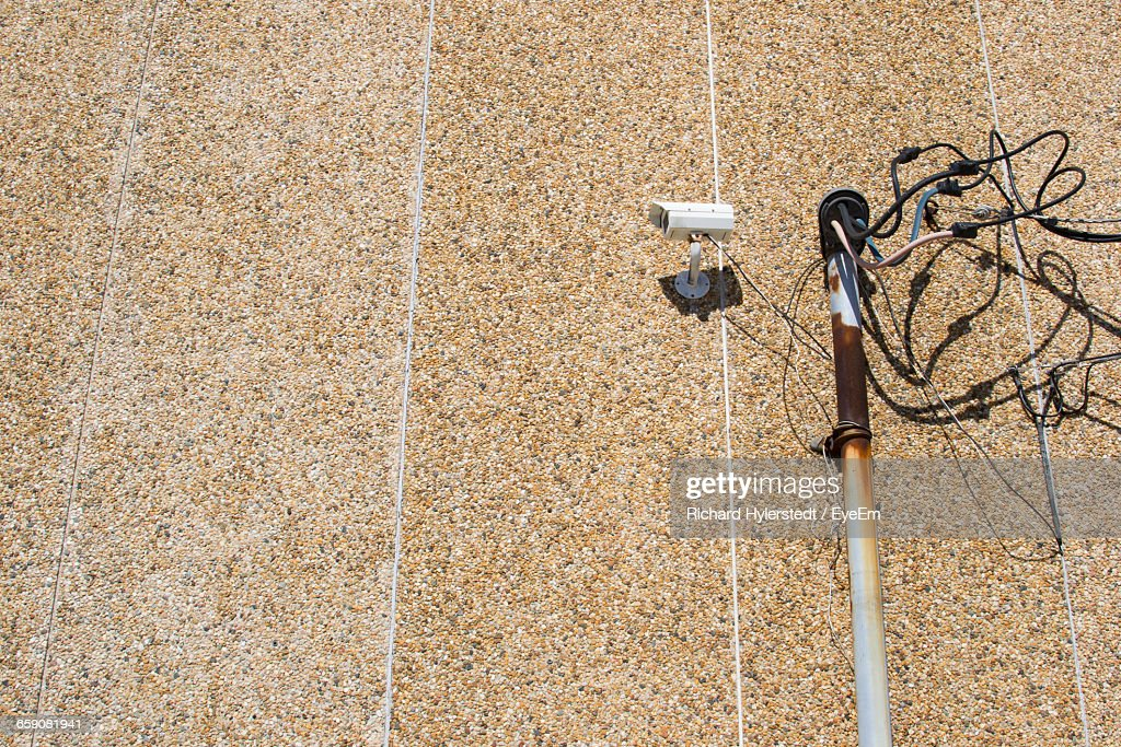 Low Angle View Of Cables And Security Camera Against Wall
