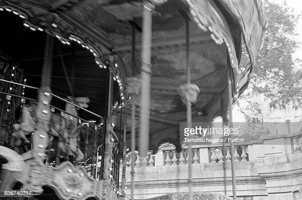 Low Angle View Of Carousel Spinning By Building At Park