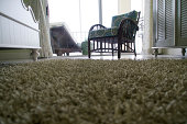 Low angle view of room looking across a shag carpet on a tile floor with furniture.