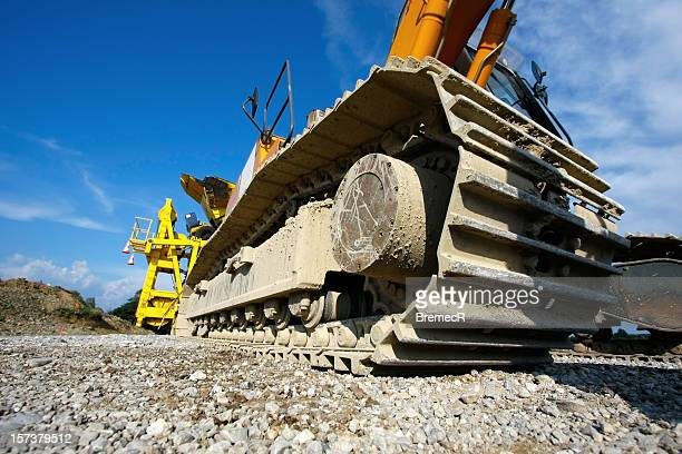 Low angle view of caterpillar tractor wheel on gravel