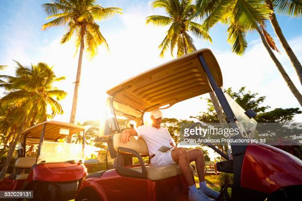 Low angle view of Caucasian golfer sitting in golf cart