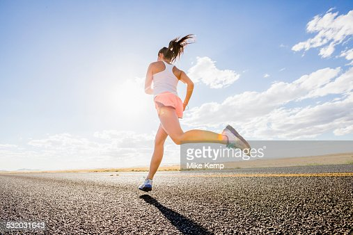 Low angle view of Caucasian woman running on remote road