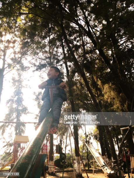 Low Angle View Of Cheerful Boy Playing On Seesaw Against Trees At Park