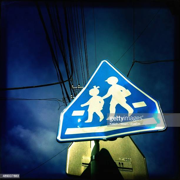 Low angle view of children crossing sign