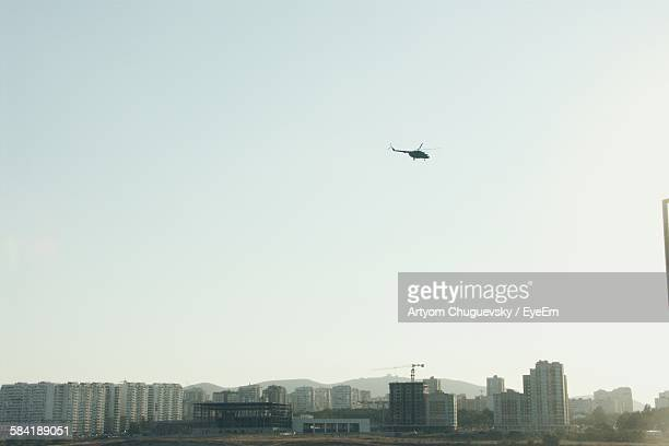 Low Angle View Of Cityscape And Helicopter Against Sky