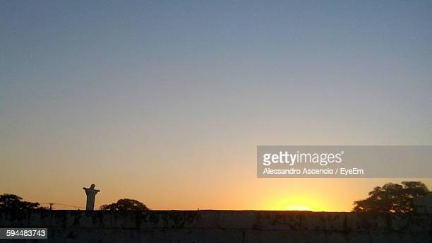 Low Angle View Of Clear Sky Over Statue And Retaining Wall During Sunset