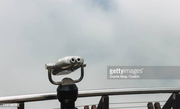 Low Angle View Of Coin-Operated Binoculars Against Cloudy Sky