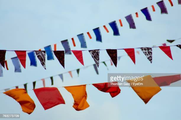Low Angle View Of Colorful Buntings Against Clear Sky