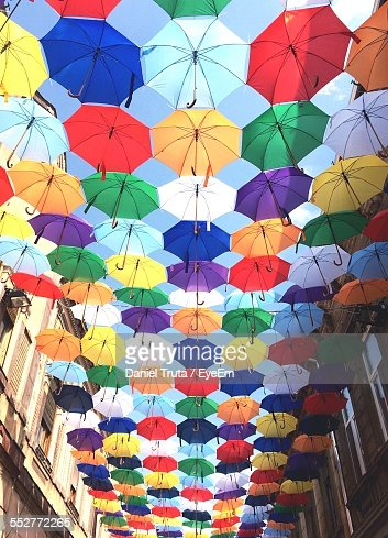 Low Angle View Of Colorful Umbrellas Hanging Amidst Buildings Against Sky