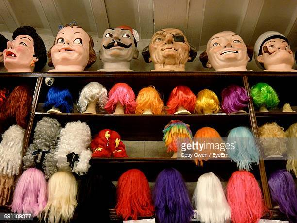 Low Angle View Of Colorful Wigs On Mannequin Heads Over Shelf At Store
