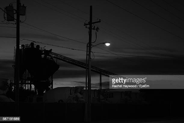 Low Angle View Of Crane And Illuminated Street Light At Construction Site