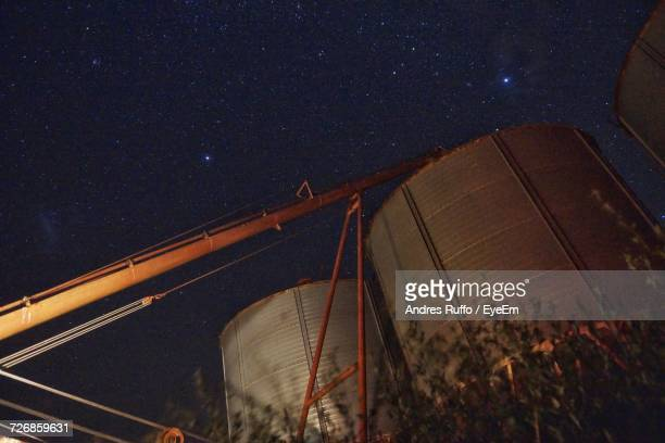 Low Angle View Of Crane By Silos Against Starry Sky At Night