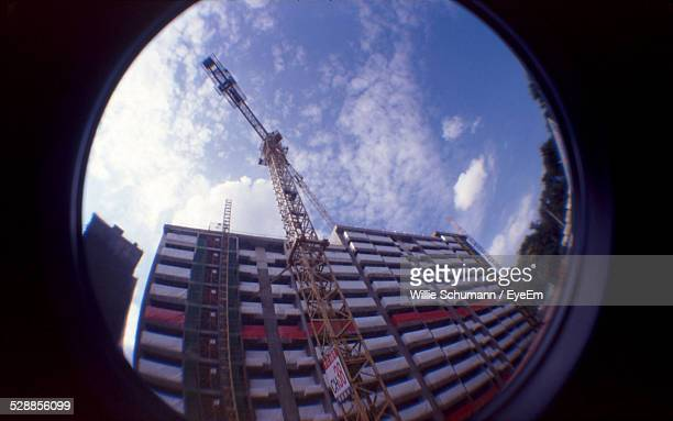 Low Angle View Of Crane Outside Building At Construction Site Seen Through Glass