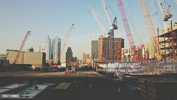 Low Angle View Of Cranes And Buildings In City Against Sky