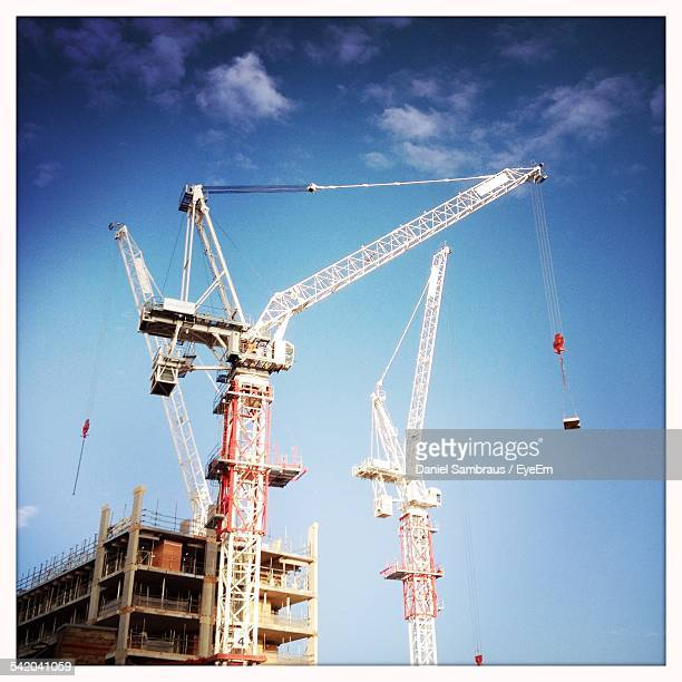Low Angle View Of Cranes At Construction Site Against Blue Sky