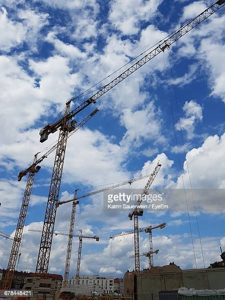 Low Angle View Of Cranes At Construction Site Against Cloudy Sky