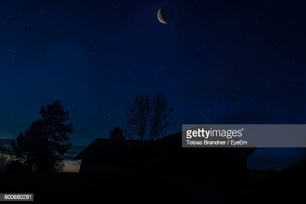 Low Angle View Of Crescent Moon Over Silhouette House
