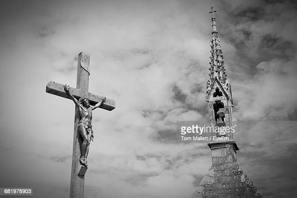 Low Angle View Of Cross Fix Statue By Bell Tower Against Cloudy Sky