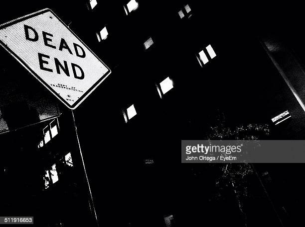 Low angle view of Dead End sign against building at night