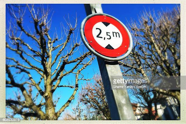Low Angle View Of Distance Sign On Pole Amidst Bare Trees Against Sky