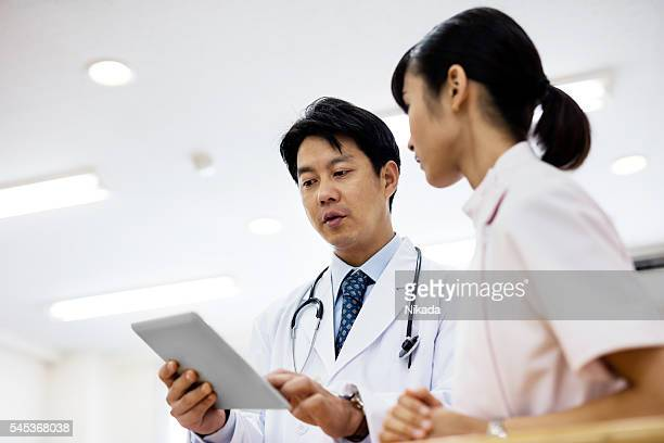 Low angle view of doctor showing digital tablet in hospital