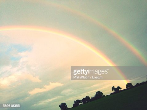 Low Angle View Of Double Rainbow Over Field