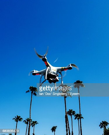 Low Angle View Of Drone And Palm Trees Against Clear Blue Sky