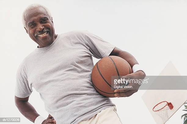 Low Angle View of Elderly Man Standing Holding a Basketball