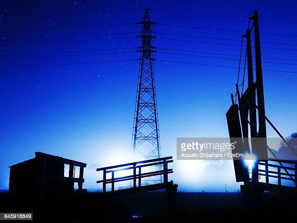 Low Angle View Of Electricity Pylon Against Blue Sky At Night
