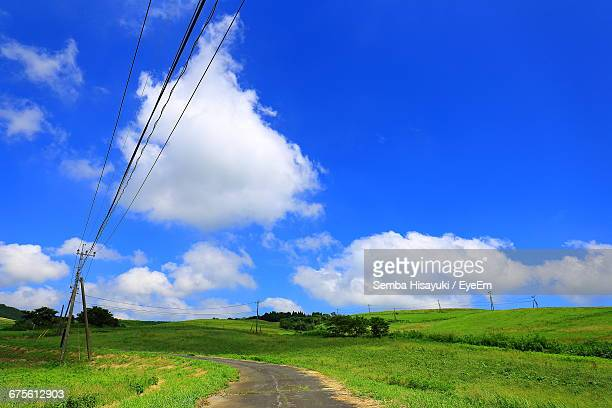 Low Angle View Of Electricity Pylon On Grassy Field Against Cloudy Blue Sky