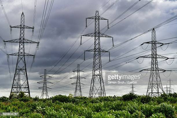 Low Angle View Of Electricity Pylons On Field Against Cloudy Sky