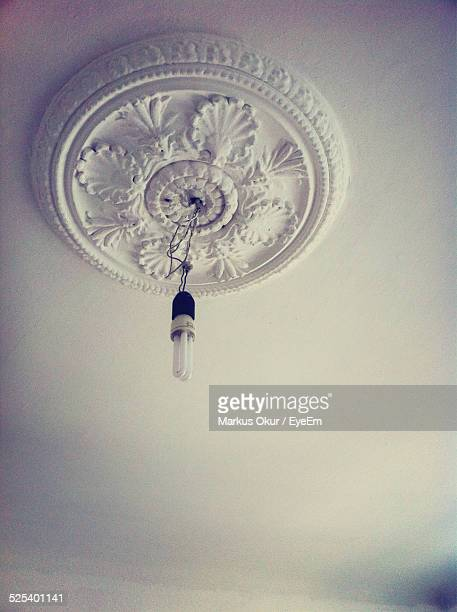Low Angle View Of Energy Efficient Light Bulb Hanging On Ceiling
