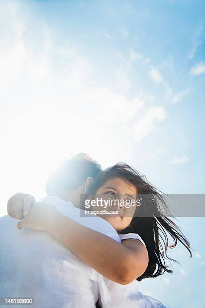 Low angle view of father and daughter embracing