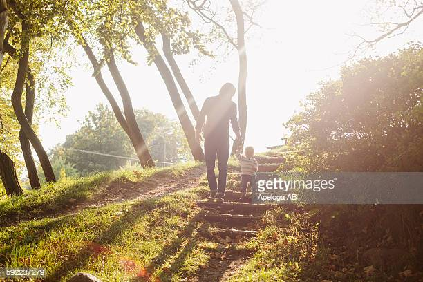 Low angle view of father and daughter standing on steps at park during sunny day