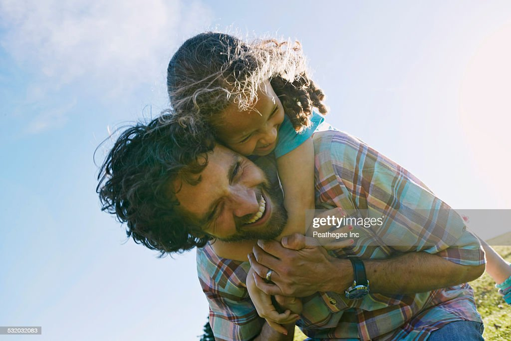 Low angle view of father carrying daughter piggyback outdoors : Stock Photo