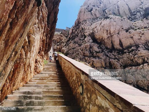 Low Angle View Of Father With Child Walking On Staircase Amidst Capo Caccia Cliffs