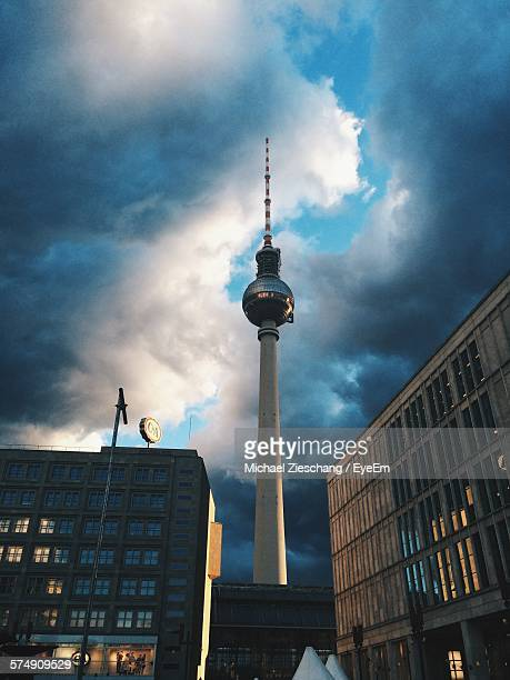 Low Angle View Of Fernsehturm And Buildings Against Cloudy Sky