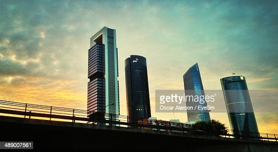 Low angle view of financial buildings against cloudy sky at dusk