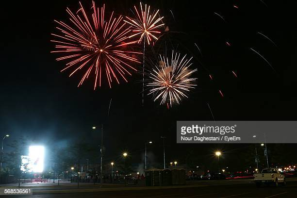 Low Angle View Of Firework Display In City At Night