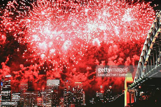 Low Angle View Of Firework Display Over Cityscape At Night