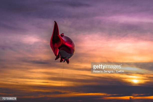 Low Angle View Of Fish Shape Helium Balloon Against Cloudy Sky During Sunset