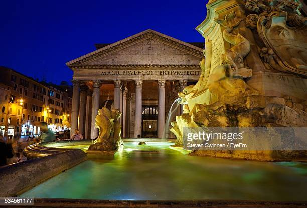 Low Angle View Of Fountain Against Pantheon At Dusk