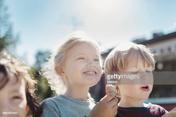 Low angle view of friends eating ice creams at yard on sunny day