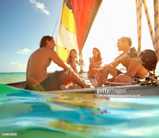Low angle view of friends sitting on sailboat in ocean