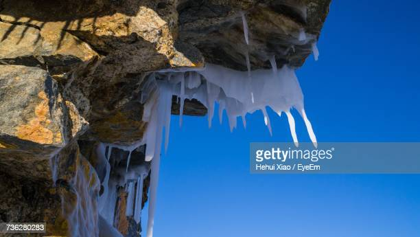 Low Angle View Of Frozen Rock Against Clear Blue Sky